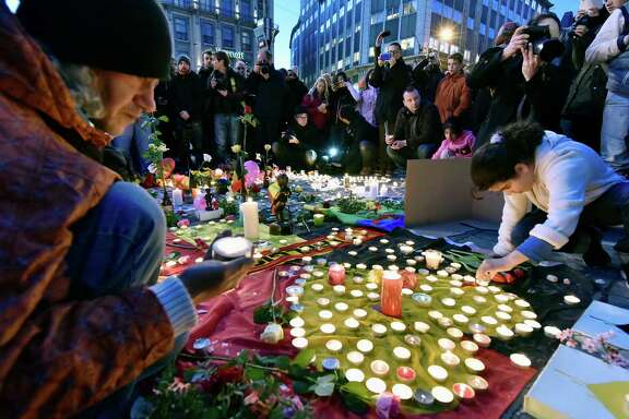 Mourners gather at Place de la Bourse in Brussels on Tuesday after deadly bombs struck the city.