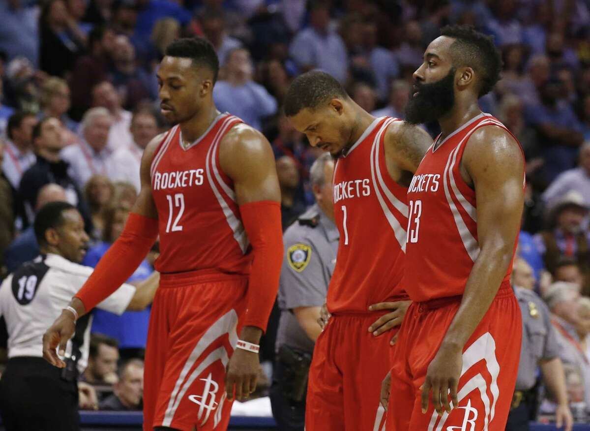 Houston Rockets center Dwight Howard (12), forward Trevor Ariza (1) and guard James Harden (13) walk off the court during a timeout in the fourth quarter of the team's NBA basketball game against the Oklahoma City Thunder in Oklahoma City, Tuesday, March 22, 2016. Oklahoma City won 111-107.