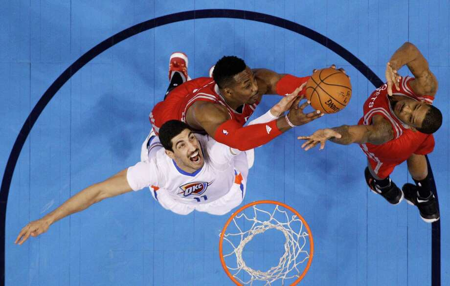 Thunder center Enes Kanter, left, and Rockets counterpart Dwight Howard give it their all for the ball on Tuesday night. Photo: Sue Ogrocki, STF / AP