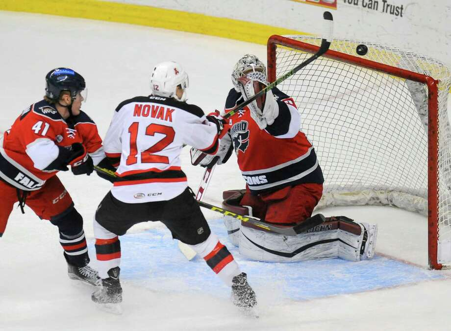 Albany Devils' Max Novak's (12) shot goes over the crossbar while being defended by Springfield Falcons' Ross Mauermann (41) and goalie Marek Langhamer (30) during the first period of an AHL hockey game in Albany, N.Y., Tuesday, March. 22, 2016. (Hans Pennink / Special to the Times Union) ORG XMIT: HP101 Photo: Hans Pennink / 10035913A