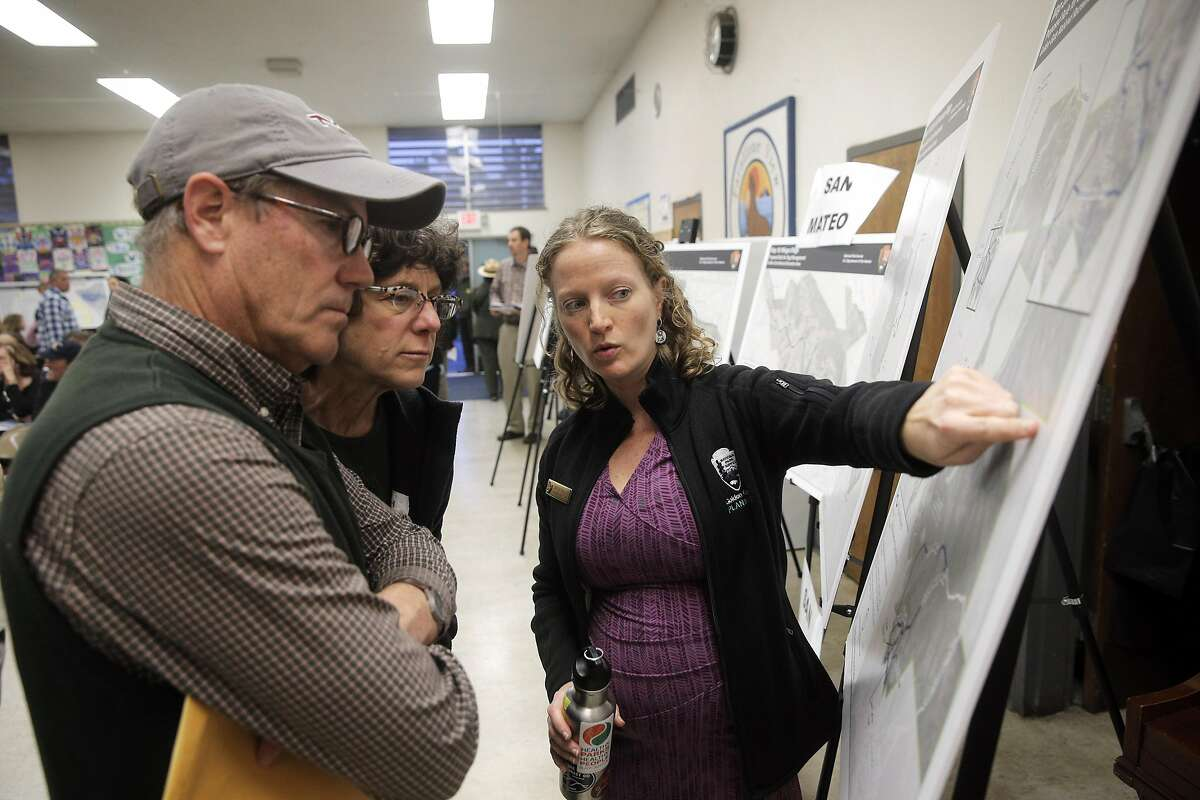 Lisa Eshman, center, Jeff Thayer, left, speak to Christine Fitzgerald as dogs owners came to voice their opinions of the proposed plan to change off-leash access to the Golden Gate National Recreation Area during a meeting with the National Park Service in Montara, Calif., on Tuesday, March 22, 2016. The National Park Service has proposed plans to restrict off-leash access for dogs in some parts of the GGNRA, eliminating them in San Mateo County.