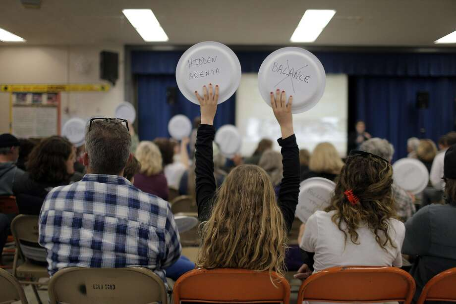 Kaitlin West, 11, holds up her paper plates with protest messages as dog owners came to voice their opinions of the proposed plan to change off-leash access to the Golden Gate National Recreation Area during a meeting with the National Park Service in Montara, Calif., on Tuesday, March 22, 2016. The National Park Service has proposed plans to restrict off-leash access for dogs in some parts of the GGNRA, eliminating them in San Mateo County. Photo: Carlos Avila Gonzalez, The Chronicle