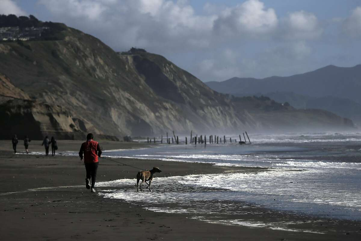 A jogger runs along the beach with his dog as they and others enjoy the area at Fort Funston in San Francisco, Calif., on Tuesday, March 22, 2016.