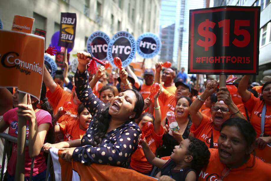 Fast food workers and supporters gather to watch for the live-streamed wage board decision in New York, July 22, 2015. On Tuesday, a California initiative which aims to hike the state's minimum wage to $15 an hour by 2021 cleared an important hurdle and qualified for the November ballot. Photo: CHANG W LEE, New York Times