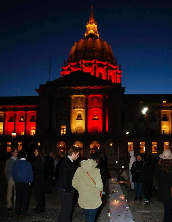San Francisco City Hall is lit with the colors of the Belgian flag as supporters for the victims of the Brussels terrorist attacks show their solidarity during a vigil and moment of silence. Photo: MONICA DAVEY, AFP/Getty Images
