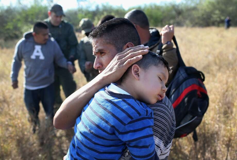 A father holds his sleeping son, 3, after they and other undocumented immmigrants were detained by Border Patrol agents on December 7, 2015 near Rio Grande City, Texas. They had just illigally crossed the U.S.-Mexico border, and he said he was bringing his family from Guanajuato, Mexico to settle in San Antonio, Texas. The number of migrant families and unaccompanied minors  crossing the border has again surged in recent months, even as the total number of illegal crossings nationwide has gone down from the previous year.  (Photo by John Moore/Getty Images) Photo: John Moore / Getty Images