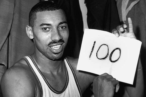 "FILE - In this March 2, 1962, file photo, Wilt Chamberlain of the Philadelphia Warriors holds a sign reading ""100"" in the dressing room in Hershey, Pa., after he scored 100 points as the Warriors defeated the New York Knickerbockers 169-147. Recordings reaching back to 1911, including coverage of the game, are being added to the Library of Congress' National Recording Registry on Wednesday, March 23, 2016. Each year the library chooses recordings that are ""culturally, historically or aesthetically significant."" This year's picks include a wide range of music from blues, jazz and rock to country and classical, but there are also recordings of radio shows, speeches, comedy and the recording of the coverage of the fourth quarter of the game that Chamberlain scored a record-shattering 100 points in a single game. (AP Photo/Paul Vathis, File)"