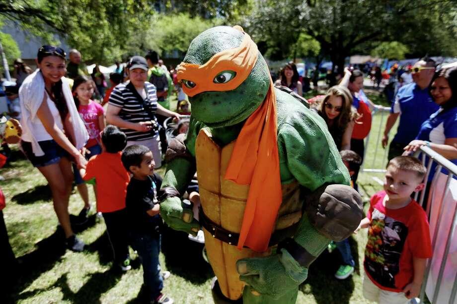 Michelangelo of the Teenage Mutant Ninja Turtles thrills the crowd at the 2015 McDonald's Houston Children's Festival.  , Photo: Gary Coronado, Staff / © 2015 Houston Chronicle