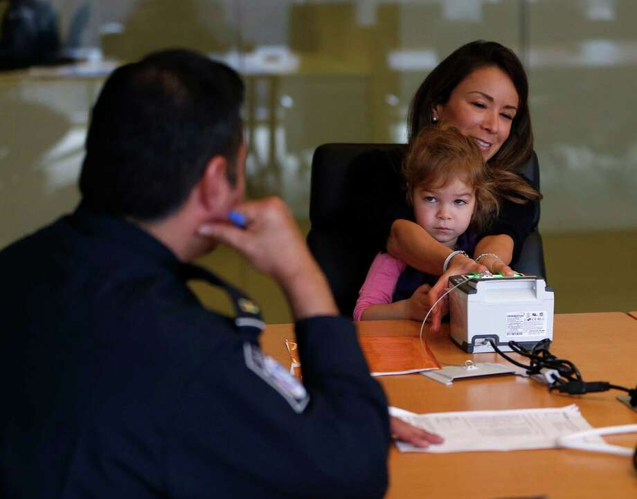 Adrianna Salinas submits fingerprints with her daughter for Customs and Border Protection officers. Photo: Karen Warren, Staff / © 2016  Houston Chronicle