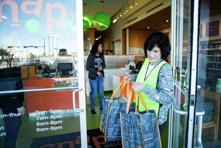 Barbara Heitman Bronstein, founder of Second Servings walks out of Snap Kitchen on Kirby Drive with prepared food donated by Snap Kitchen. The food will be redirected to local charities that service the hungry. Thursday, Jan. 28, 2016, in Houston. ( Marie D. De Jesus / Houston Chronicle )