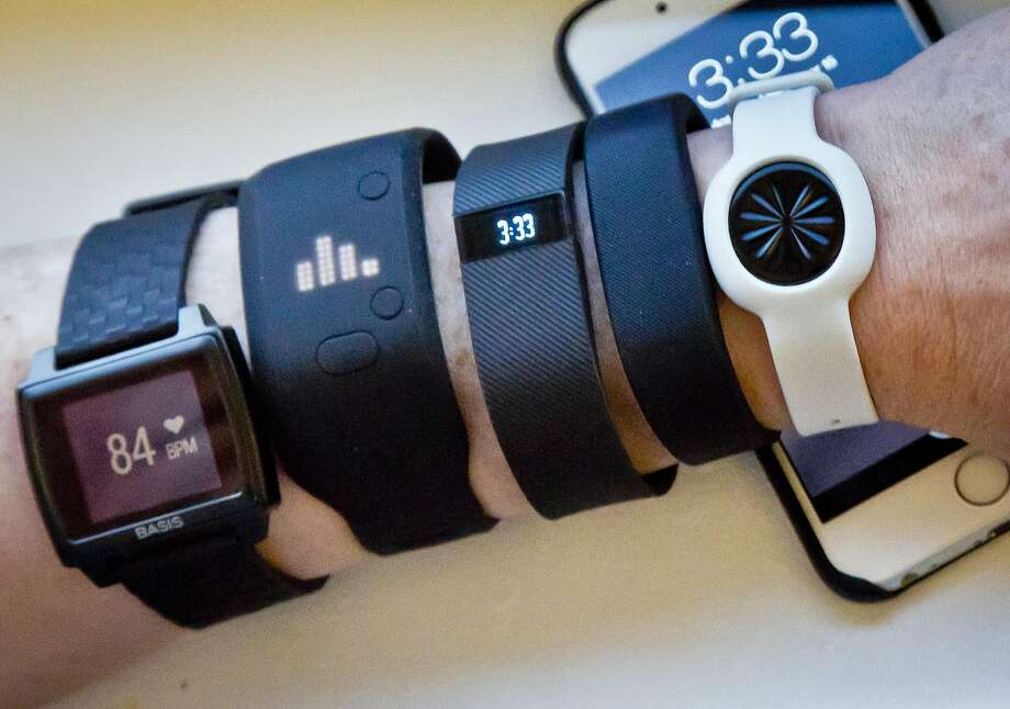 In this Dec. 15, 2014 file photo, fitness trackers, from left, Basis Peak, Adidas Fit Smart, Fitbit Charge, Sony SmartBand, and Jawbone Move, are posed for a photo next to an iPhone, in New York. Photo: Bebeto Matthews, Associated Press
