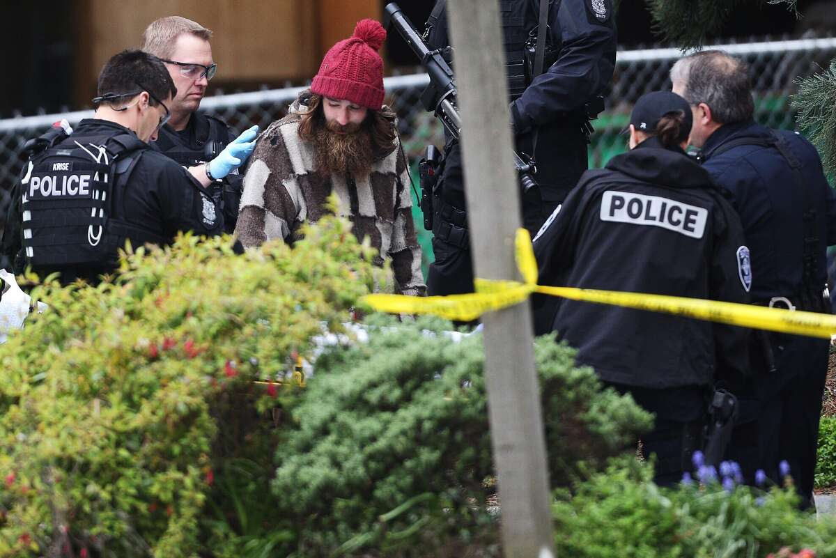 After coming down from an 80-foot tree next to Seattle's downtown Macy's, a man is surrounded by police on Wednesday, March 23, 2016. The man spent 24 hours in the tree. He was taken away by an ambulance.