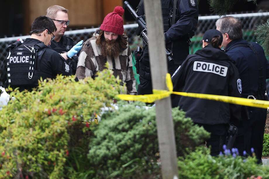 After coming down from an 80-foot tree next to Seattle's downtown Macy's, a man is surrounded by police on Wednesday, March 23, 2016. The man spent 24 hours in the tree. He was taken away by an ambulance. Photo: Grant Hindsley/seattlepi.com / Copyright 2016. All rights reserved.