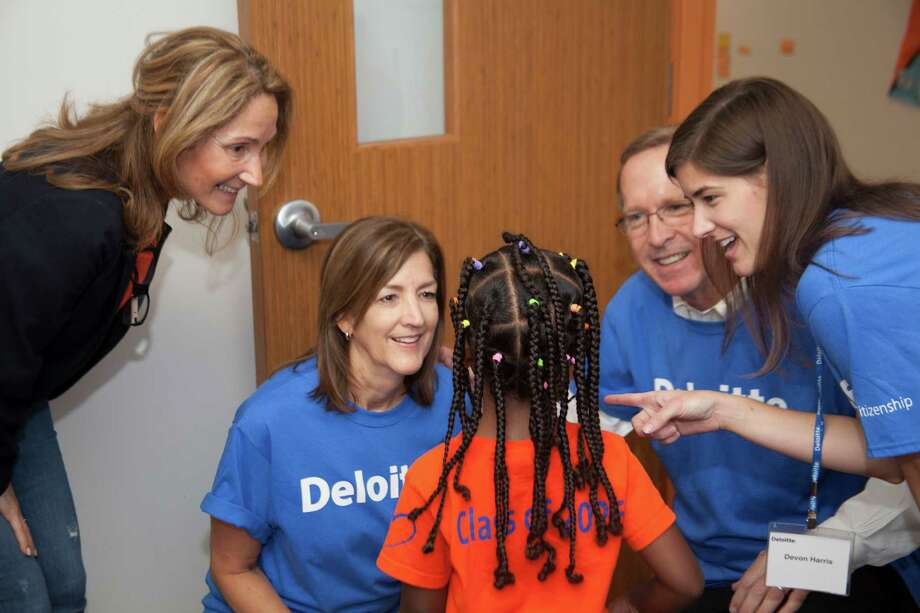 From left to right: Alma Salman, Head of Schools for KIPP CONNECT Houston Primary and KIPP CONNECT Houston Middle School; Anne Taylor, Houston Managing Partner, Deloitte LLP; A KIPP student; Neil Bush, Chairman of the  Barbara Bush Houston Literacy Foundation; Devon Harris. Deloitte volunteers engaged 500 elementary students across three Houston area schools using custom developed curriculum and fun activities focused on importance of literacy and love of reading during last year's Impact Day. Each student was given a book for their home library and a brochure for parents encouraging them to read together at least 15 minutes per day. Photo: Contributed