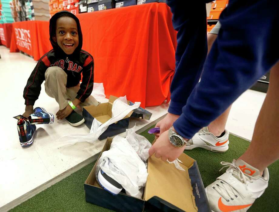 "Christopher tries on ""Star Wars"" shoes with the help of Cullen Stewart, 14. Christopher was among about 70 children ages 4-17 from the Star of Hope's Randy and Kathy Tabor Transitional Living Center who shopped for new shoes at Sports Authority. Photo: Karen Warren, Staff / © 2015  Houston Chronicle"