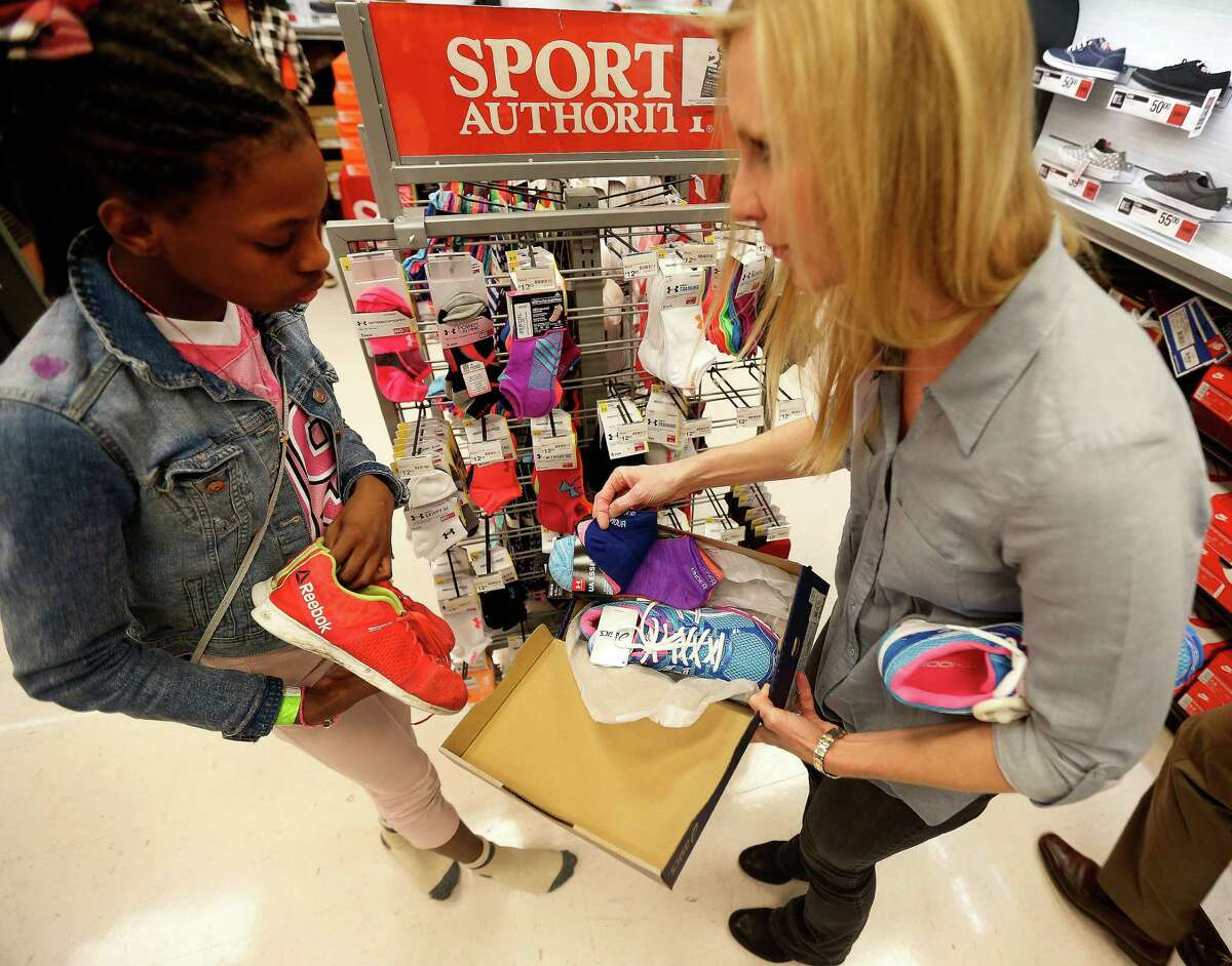 Heather Holmes, right helps find the perfect pair of socks to go with Phyllis' new sneakers, as she and 70 children aged 4-17 from the Star of Hope's Randy and Kathy Tabor Transitional Living Center shop for new shoes at Houston's Sports Authority store on Post Oak, assisted by Trees of Hope Guild on Monday, Jan. 4, 2016, in Houston. ( Karen Warren / Houston Chronicle )