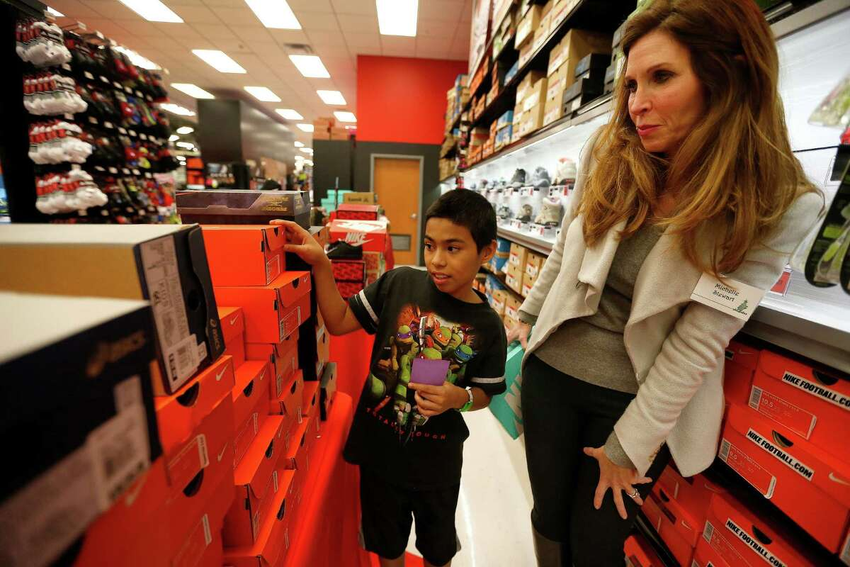 """Jorge shops with Michelle Stewart as he and about 70 children aged 4-17 from the Star of Hope's Randy and Kathy Tabor Transitional Living Center shop for new shoes at Houstoné¢Ã©""""é´s Sports Authority store on Post Oak, assisted by Trees of Hope Guild on Monday, Jan. 4, 2016, in Houston. ( Karen Warren / Houston Chronicle )"""