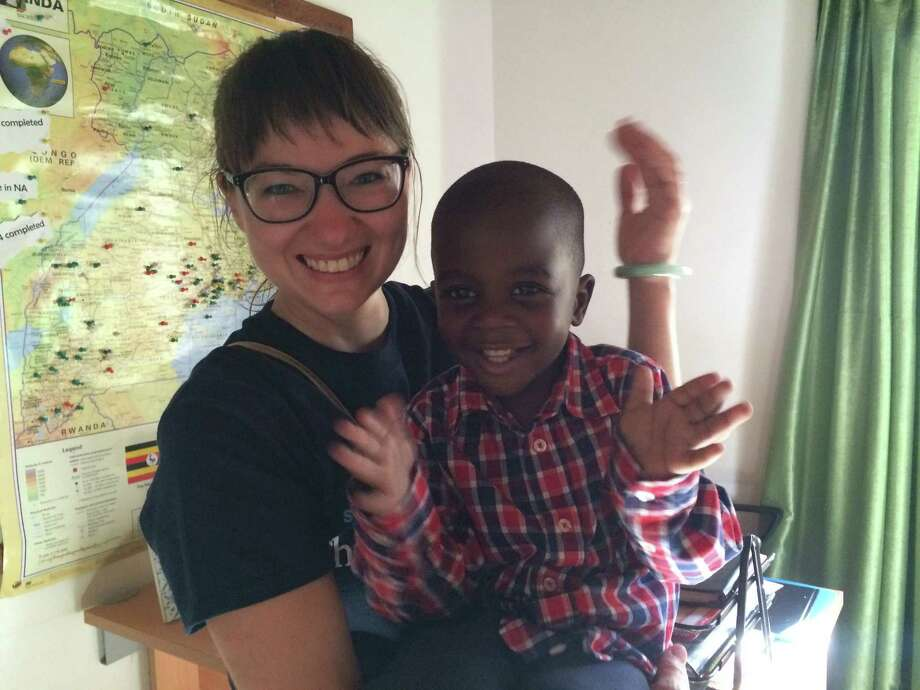 Dan shares his excitement with Mari Krueger, a volunteer transporter with the Children's Heart Project, moments after their long journey from Texas to Uganda reunites him with his father. Photo: Courtesy / handout