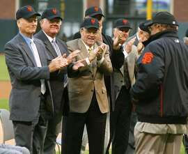 Members of the 1954 champion New York Giants, from left, Harvey Gentry, Al Worthington and Joe Garagiola applaud teammate Willie Mays, right, on Saturday July 31, 2004, in San Francisco. Players on the 1954 team were honored in a ceremony before the San Francisco Giants' game against the St. Louis Cardinals. (AP Photo/George Nikitin)