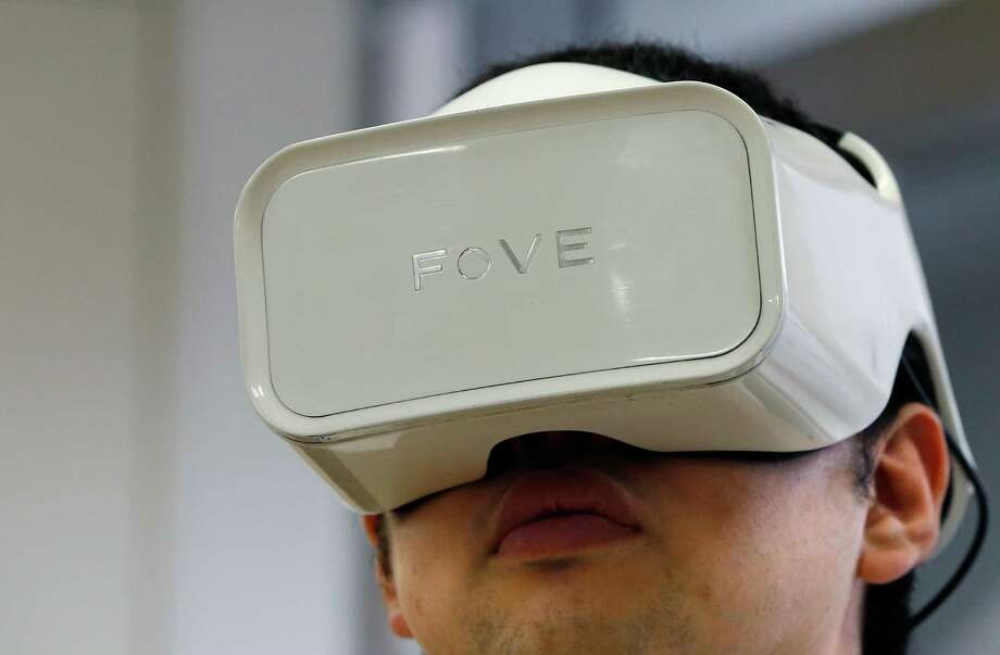 In this March 7, 2016 photo, Fove's staff wearing an eye-tracking headset goggles demonstrates virtual reality at his office in Tokyo. San Francisco-based startup Fove has developed eye-tracking for virtual reality - that kernel of technology many feel is key for the illusion of becoming immersed in a setting. Fove has devised a way to use tiny infrared sensors inside headset goggles to monitor the movements of a wearer's pupils. (AP Photo/Shizuo Kambayashi) Photo: Shizuo Kambayashi, STF / AP / AP