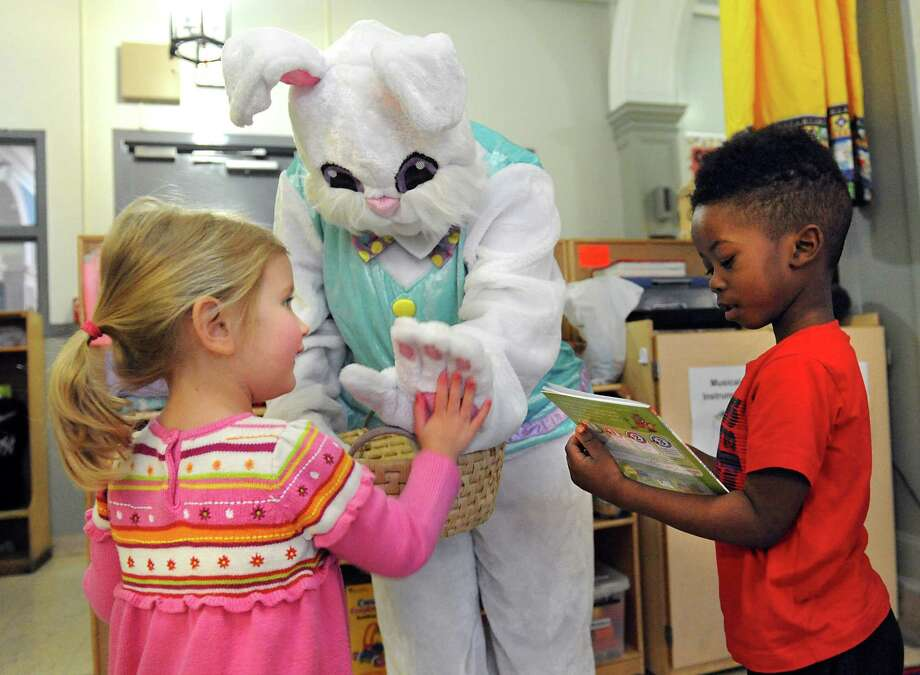 Colby K., 3, slaps five with the Easter Bunny before receiving a coloring book like Christian J., 4, right, got at the Unity Sunshine Program III preschool class 2 on  Wednesday, March 23, 2016 in Troy, N.Y.  (Lori Van Buren / Times Union) Photo: Lori Van Buren / 20035942A