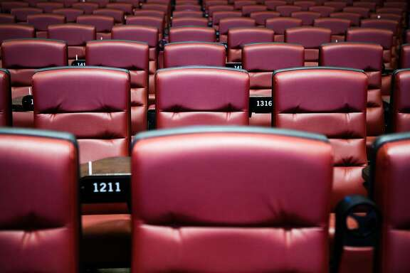 Red seats with tray tables for food can be seen in the main theater of the Alamo Drafthouse at the New Mission Theater in San Francisco, California on Friday, December 4, 2015.