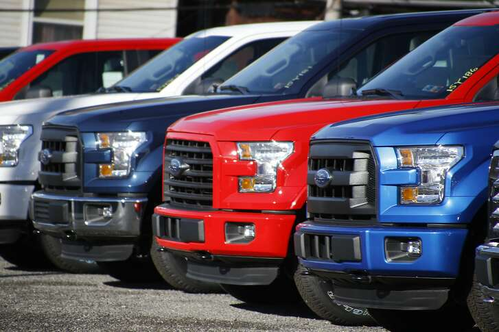 In this photo made on Thursday, Nov. 19, 2015, a row of 2015 Ford F-150 pickup trucks are parked on the sales lot at Butler County Ford in Butler, Pa. Two auto sales forecasting companies say Americans will buy more cars and trucks in December 2015 than any other month in more than a decade. LMC Automotive and J.D. Power are predicting that U.S. sales will hit 1.71 million this month, the highest number since sales reached 1.8 million in July of 2005. (AP Photo/Keith Srakocic)