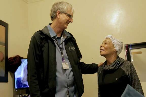 Maurice Ruark, a resident nurse with Hospice by the Bay, comforts Iris West in her room at Windsor Hotel in the Tenderloin neighborhood on Tuesday, March 1, 2016 in San Francisco, Calif. Ruark has been working with terminally ill patients in the Tenderloin for 27 years.