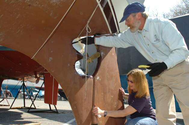 "Ellin Hillestad and George McBride fixing up Hillestad's boat, called Lille Venn which translates as ""Little Friend"" in Norwegian, on Sunday, April 4, 2010. Their boat had been stored near the Old Greenwich Yacht club. The Old Greenwich Yacht launch begins on April 24. The Greenwich town docks will open on April 15. Photo: Helen Neafsey / Greenwich Time"