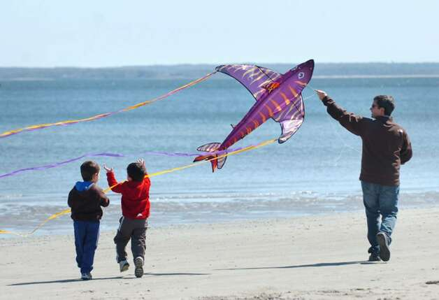 George D'Angelo, of Riverside, plays the Pied Piper with his fish kite as his two sons, Derek, 4, left, and Jake, 3, center, follow along during the annual Kite Flying Festival at Greenwich Point, Saturday afternoon, April 10, 2010. Photo: Bob Luckey / Greenwich Time