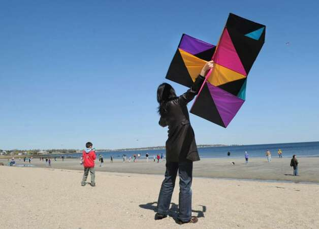 Wenjin Qiu of Greenwich holds onto her box kite as her son, Yikuan Zhou, 6, left, attempts to pull on the string to get it airborne during the annual Kite Flying Festival at Greenwich Point, Saturday afternoon, April 10, 2010, Greenwich, Conn.  The pair were unsuccessful at getting the kite into the sky. Photo: Bob Luckey / Greenwich Time