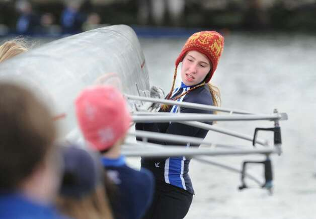 Grace Ingalls of the Greenwich Club crew team helps put her team's shell into Greenwich Harbor during the start of the NYPPEX Greenwich Invitational Sprints, April 10, 2010. Photo: Bob Luckey / Greenwich Time