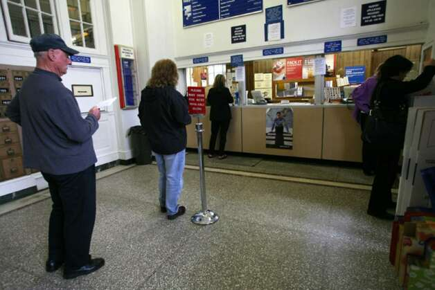 Patrons at the Greenwich Avenue Post Office wait online to have their mail processed Friday afternoon. Photo: David Ames / Greenwich Time