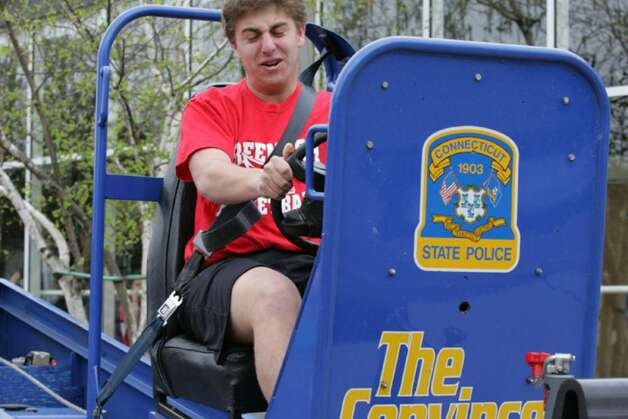Greenwich High School student Sam Latto takes a ride on The Convincer, which simulates a low-speed car collision, during the last day of Alcohol Awareness Week Friday at the school. Photo: David Ames, David Ames/For Greenwich Time / Greenwich Time