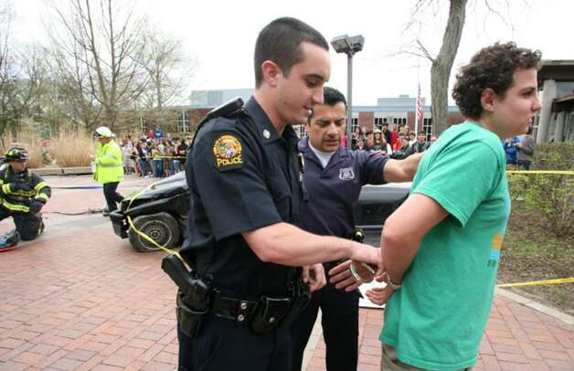 Greenwich High School junior Alexis Bedos is arrested and handcuffed by Greenwich Police Officers Matt Nardi, left, and School Resource Officer Carlos Franco during a mock drunken-driving accident Friday afternoon as part of the school's final day of Alcohol Awareness Week. Photo: David Ames, David Ames/For Greenwich Time / Greenwich Time