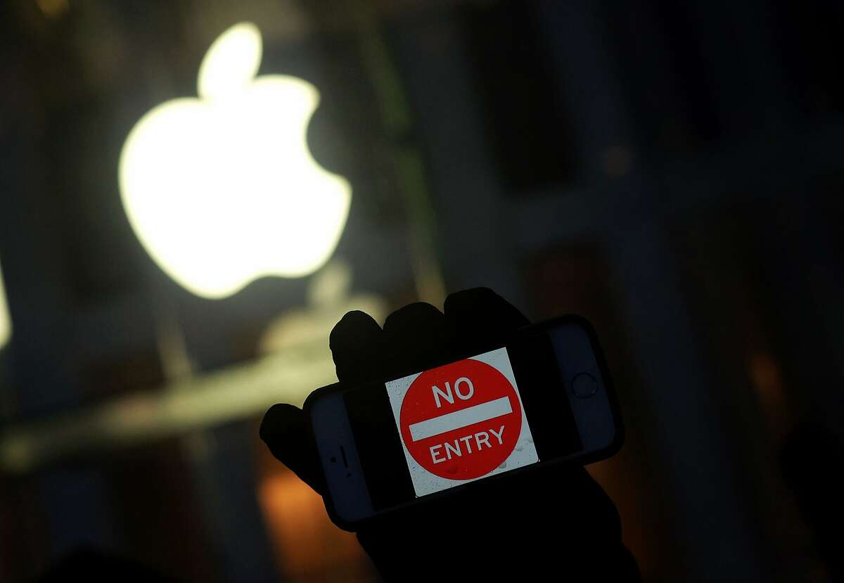 """(FILES) This file photo taken on February 23, 2016 shows an anti-government protester holding his iPhone with a sign """"No Entry"""" during a demonstration near the Apple store on Fifth Avenue in New York. The US Justice Department on March 21, 2016 filed a request to postpone a crucial hearing with Apple on accessing the iPhone of one of the San Bernardino attackers, citing new leads in the case. """"On Sunday, March 20, 2016, an outside party demonstrated to the FBI a possible method for unlocking (Syed) Farook's iPhone,"""" prosecutors said in a filing. """"Testing is required to determine whether it is a viable method that will not compromise data on Farook's iPhone. """"If the method is viable, it should eliminate the need for the assistance from Apple Inc. set forth in the All Writs Act Order in this case."""" Prosecutors requested that Tuesday's hearing before a federal judge in California be cancelled in order to allow time for testing the new method, and proposed filing a status report with the court by April 5. The high-stakes case has pitted Apple against the FBI, which sought the tech giant's help in unlocking the iPhone of Farook, who, along with his wife, was behind the December 2 terror attack in San Bernardino that left 14 people dead. jz/oh / AFP PHOTO / Jewel SamadJEWEL SAMAD/AFP/Getty Images"""