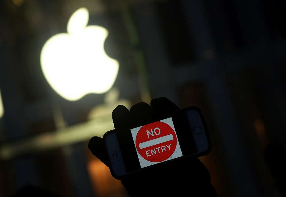 An antigovernment protester holds his iPhone during a New York demonstration near the Fifth Avenue Apple Store last month. Photo: JEWEL SAMAD, AFP/Getty Images