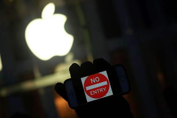 "(FILES) This file photo taken on February 23, 2016 shows an anti-government protester holding his iPhone with a sign ""No Entry"" during a demonstration near the Apple store on Fifth Avenue in New York. The US Justice Department on March 21, 2016 filed a request to postpone a crucial hearing with Apple on accessing the iPhone of one of the San Bernardino attackers, citing new leads in the case. ""On Sunday, March 20, 2016, an outside party demonstrated to the FBI a possible method for unlocking (Syed) Farook's iPhone,"" prosecutors said in a filing. ""Testing is required to determine whether it is a viable method that will not compromise data on Farook's iPhone.  ""If the method is viable, it should eliminate the need for the assistance from Apple Inc. set forth in the All Writs Act Order in this case.""  Prosecutors requested that Tuesday's hearing before a federal judge in California be cancelled in order to allow time for testing the new method, and proposed filing a status report with the court by April 5.  The high-stakes case has pitted Apple against the FBI, which sought the tech giant's help in unlocking the iPhone of Farook, who, along with his wife, was behind the December 2 terror attack in San Bernardino that left 14 people dead.  jz/oh  / AFP PHOTO / Jewel SamadJEWEL SAMAD/AFP/Getty Images"