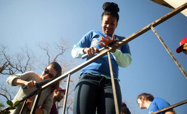 Volunteer Deneesha Jones, right, uses a wire brush on a rail as she, and other volunteers work on the Blue Triangle Community Center during Martin Luther King Jr. Day, Monday, Jan. 18, 2016, in Houston. The 2016 NCAA(R) Men's Final Four(R) Local Organizing Committee collaborated with Mission Continues, to organize 300 volunteers as they cleaned, organized and beautified the community center in the Third Ward, which serves hundreds of people.