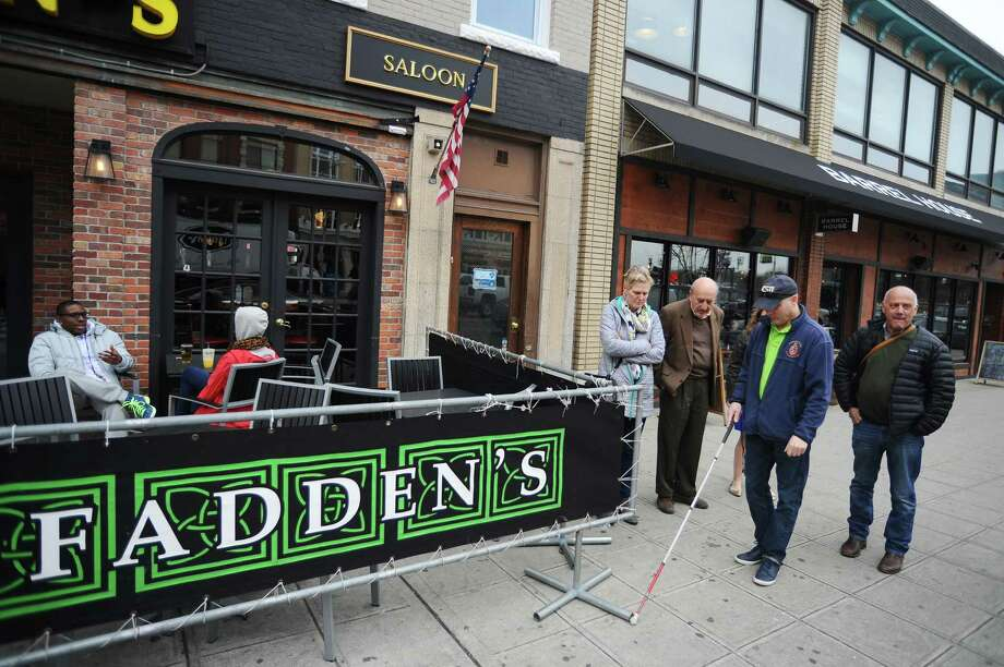 From right, Stamford Access For All (A4A) Committee Chairman Frank Mercede, Phil Magalnick, Marty Levine and Kris Burbank inspect the outdoor seating arrangement of McFadden's on Main Street  during A4A's downtown walkthrough on Wednesday, March 23, 2016. The walkthrough was intended to catch problem areas before the increase in outdoor eating areas brought on by warm weather, then fix them in time so pedestrians will have clear sidewalks. Photo: Michael Cummo / Hearst Connecticut Media / Stamford Advocate