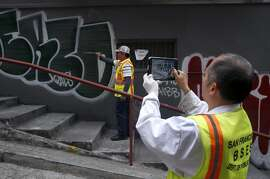 Lorenzo Soriano (left) and Yu Cheng of the Department of Public Works photographs graffiti on a building in Chinatown's Vinton Alley before covering it with a fresh coat of paint in San Francisco, Calif. on Friday, Aug. 21, 2015. The crew uploads the photographs to the city's 311 website where they will be collected and used for possible legal action. The city attorney's office is suing a serial tagger known as Cozy Terry and is seeking more than $50,000 in damages for repeatedly defacing city property.