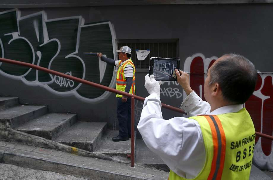 Lorenzo Soriano (left) and Yu Cheng of the Department of Public Works photographs graffiti on a building in Chinatown's Vinton Alley before covering it with a fresh coat of paint last year. Photo: Paul Chinn, The Chronicle