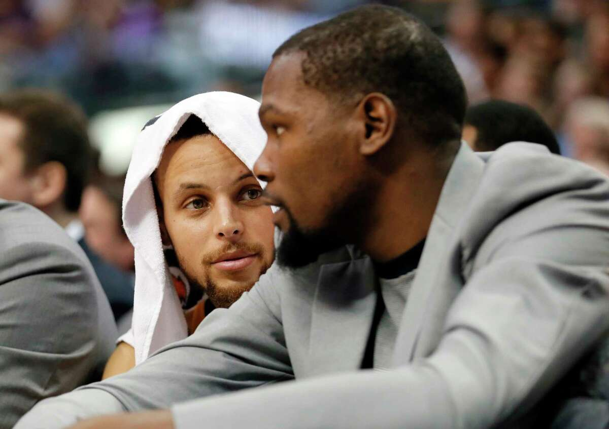 Golden State Warriors guard Stephen Curry, left, talks with Kevin Durant, right, in the first half of an NBA basketball game against the Dallas Mavericks on Tuesday, March 21, 2017, in Dallas. (AP Photo/Tony Gutierrez)