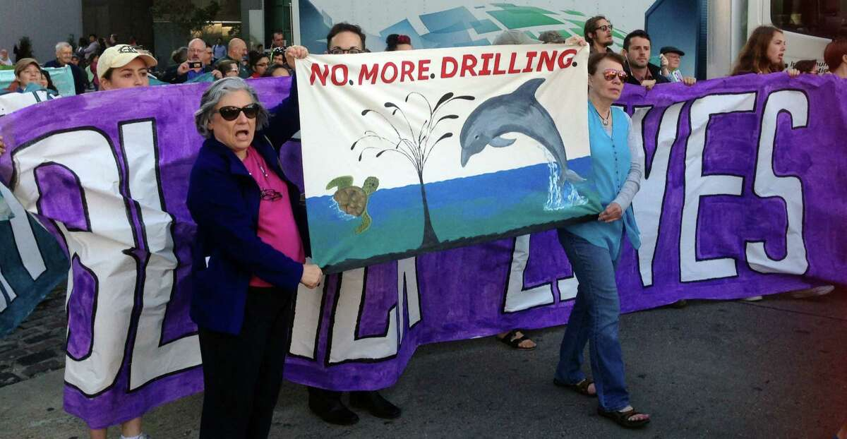 Environmentalists opposed to drilling in the Gulf of Mexico hold signs and chant slogans as they walk toward the Superdome to protest a federal government sale of oil and gas leases in the Gulf held in New Orleans, Wednesday, March 23, 2016. Federal officials say environmental protesters who demonstrated during the sale of oil and gas leases did not hold up the sale. Janice Schneider of the Department of Interior says no concerns were encountered about the protests Wednesday. (AP Photo/Rebecca Santana)