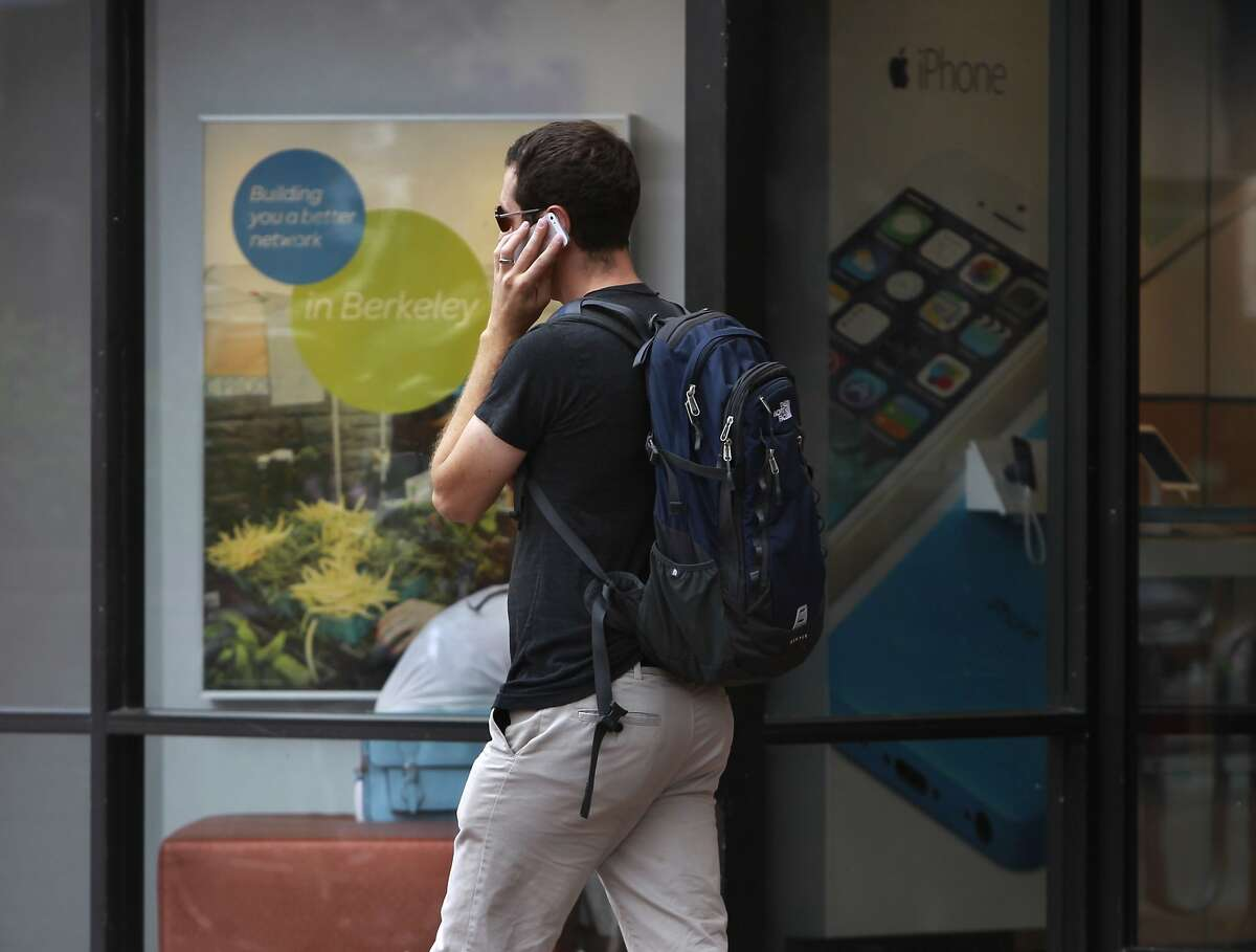 A man talks on his phone while walking past an AT&T store on Shattuck Avenue in Berkeley, Calif. on Saturday, July 12, 2014. Berkeley city officials are considering an ordinance requiring cell phone companies to place stickers on phones warning of brain cancer.