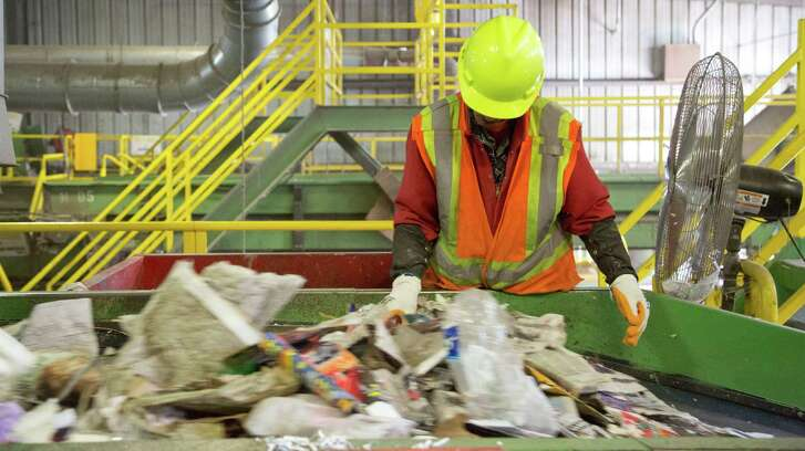 A Waste Management employee removes non-recyclable materials from a conveyor belt at the company's recycling facility in southwest Houston.