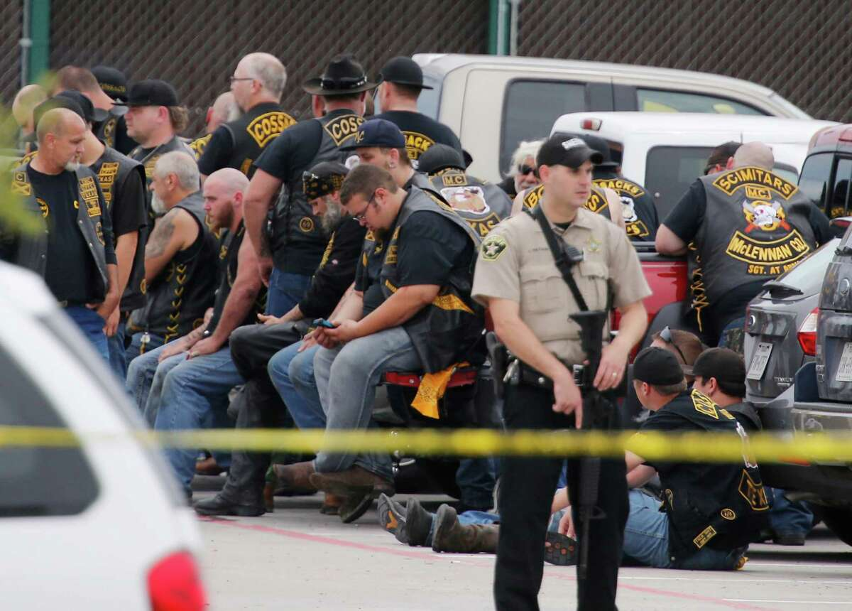 A McLennan County deputy guards a group of bikers after the melee on May 17, 2015. Over 140 bikers have now been indicted, but no case has gone to trial yet.