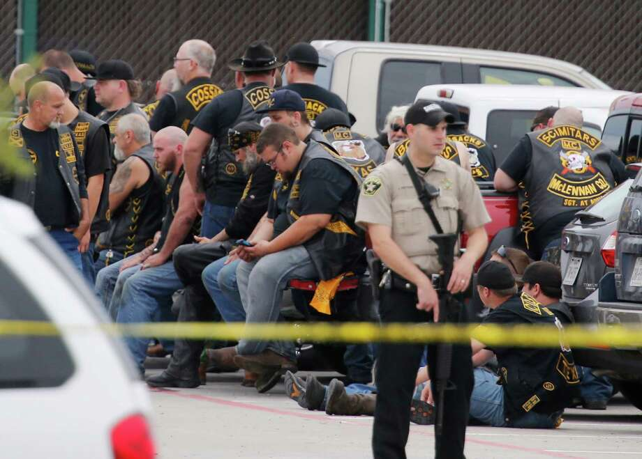 A McLennan County deputy guards a group of bikers after the melee on May 17, 2015. Over 140 bikers have now been indicted, but no case has gone to trial yet.  Photo: Rod Aydelotte, MBO / Waco Tribune-Herald
