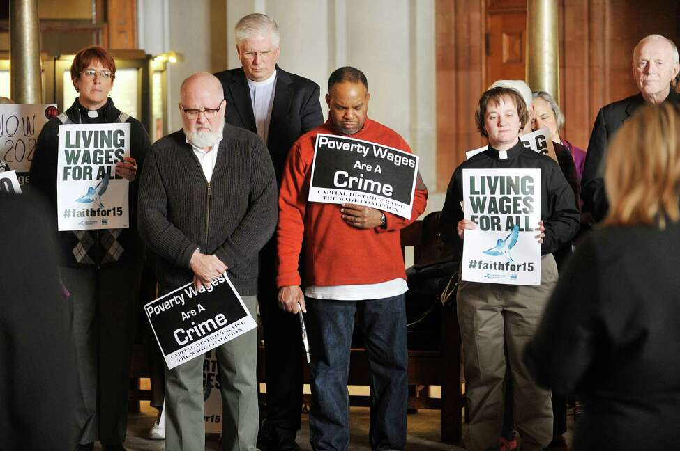 People pray as a coalition of faith groups held a rally calling on legislators to pass an increase in the minimum wage to $15 at the Capitol on Monday, March 21, 2016 in Albany, N.Y. (Paul Buckowski / Times Union)