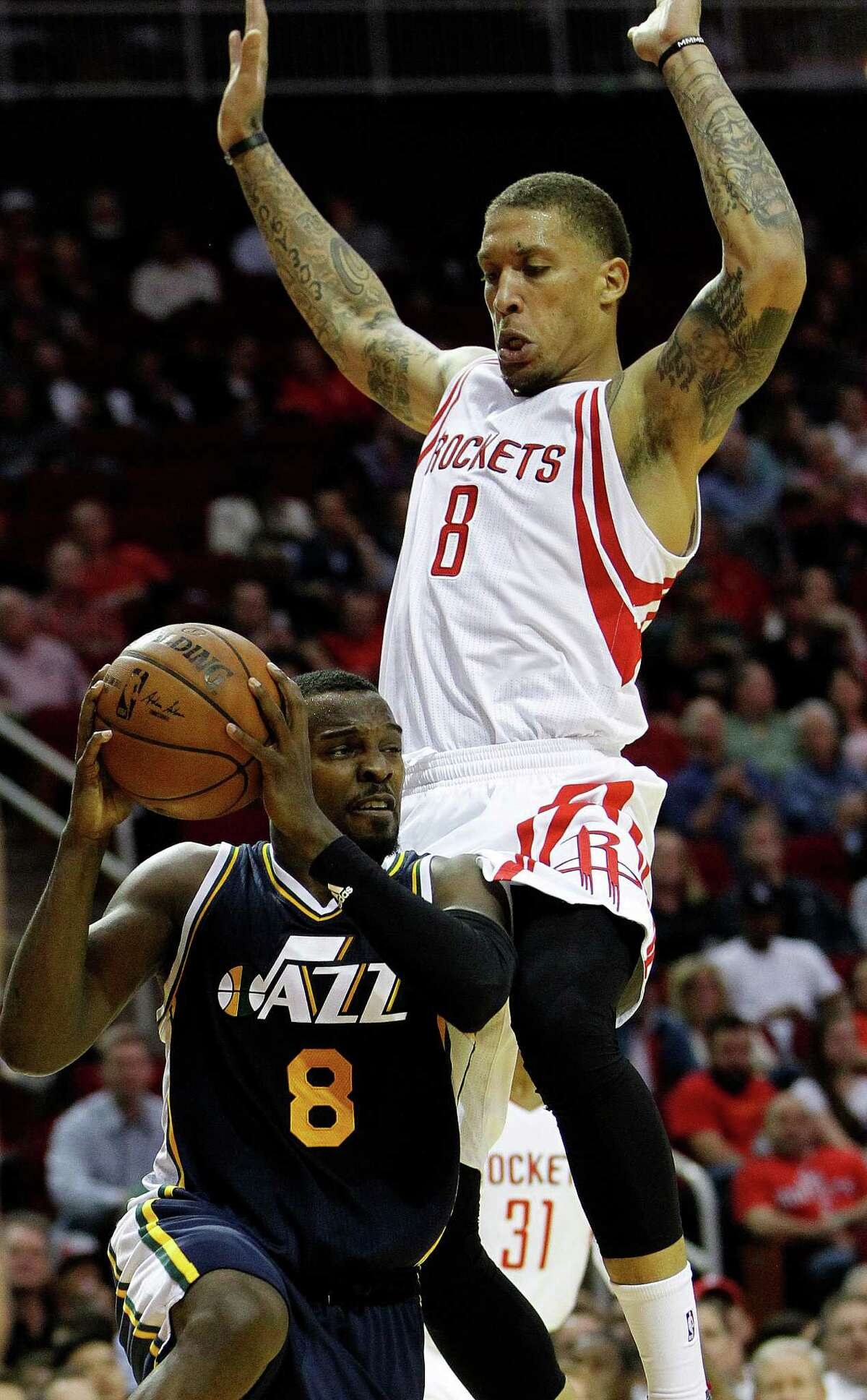Utah Jazz guard Shelvin Mack (8) goes up against Houston Rockets forward Michael Beasley (8) under the basket during the first half of an NBA basketball game at Toyota Center, Wednesday, March 23, 2016.